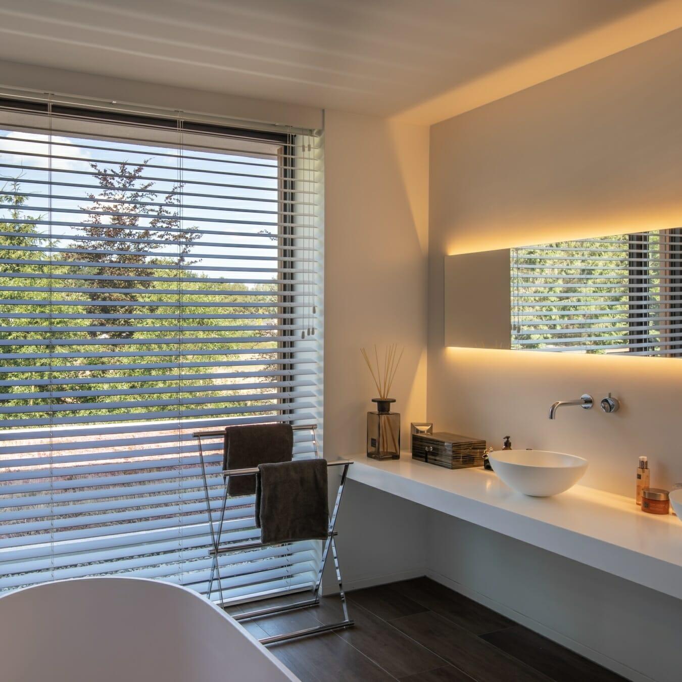 Witte houten jaloezieën in de badkamer