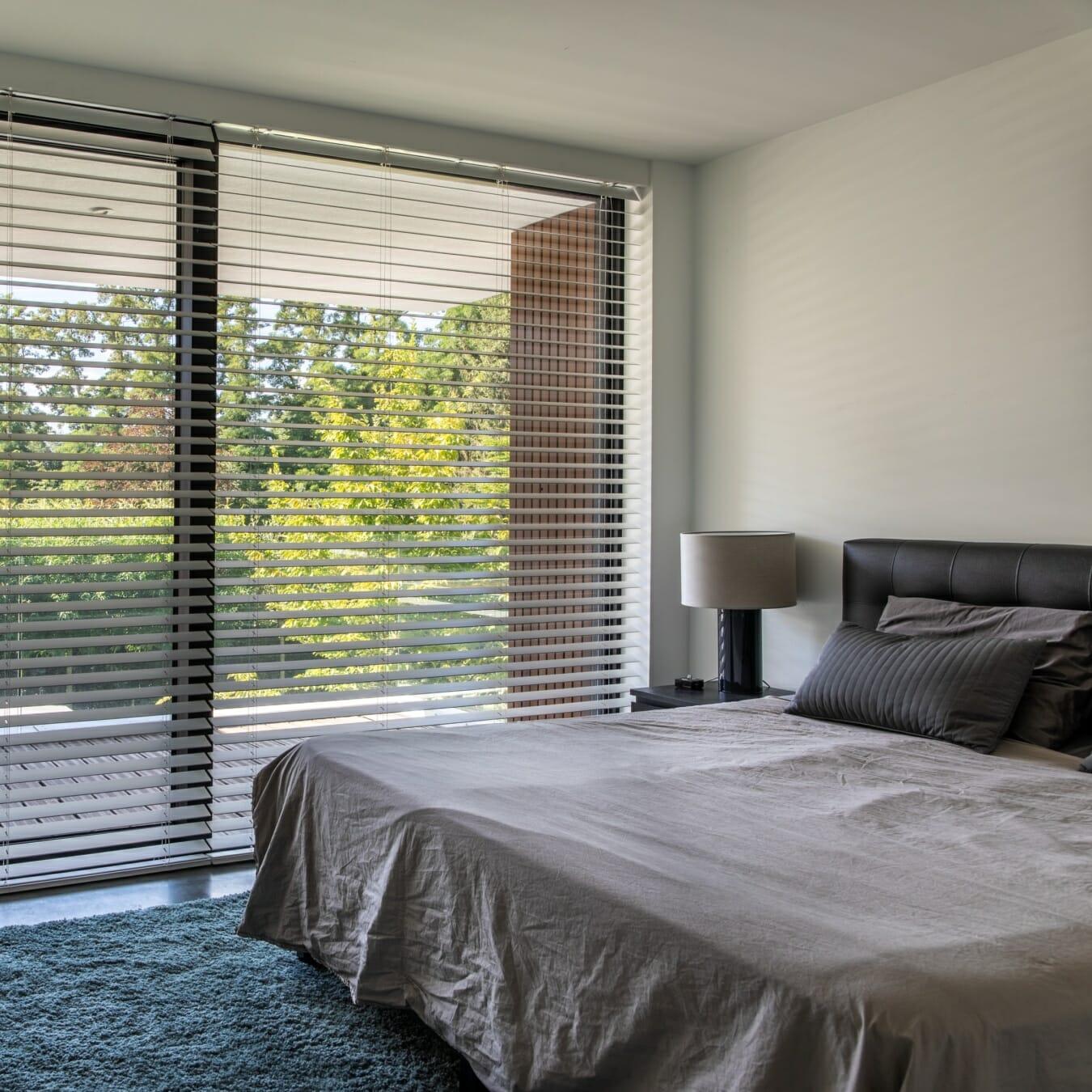 Witte houten jaloezieën in de slaapkamer